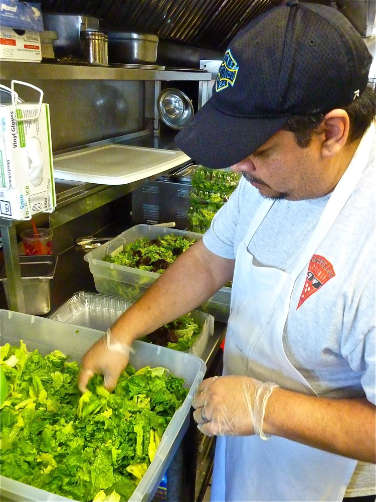 DJ Gomes makes a fresh salad at Carmella's Pizzeria in Middletown, R.I.