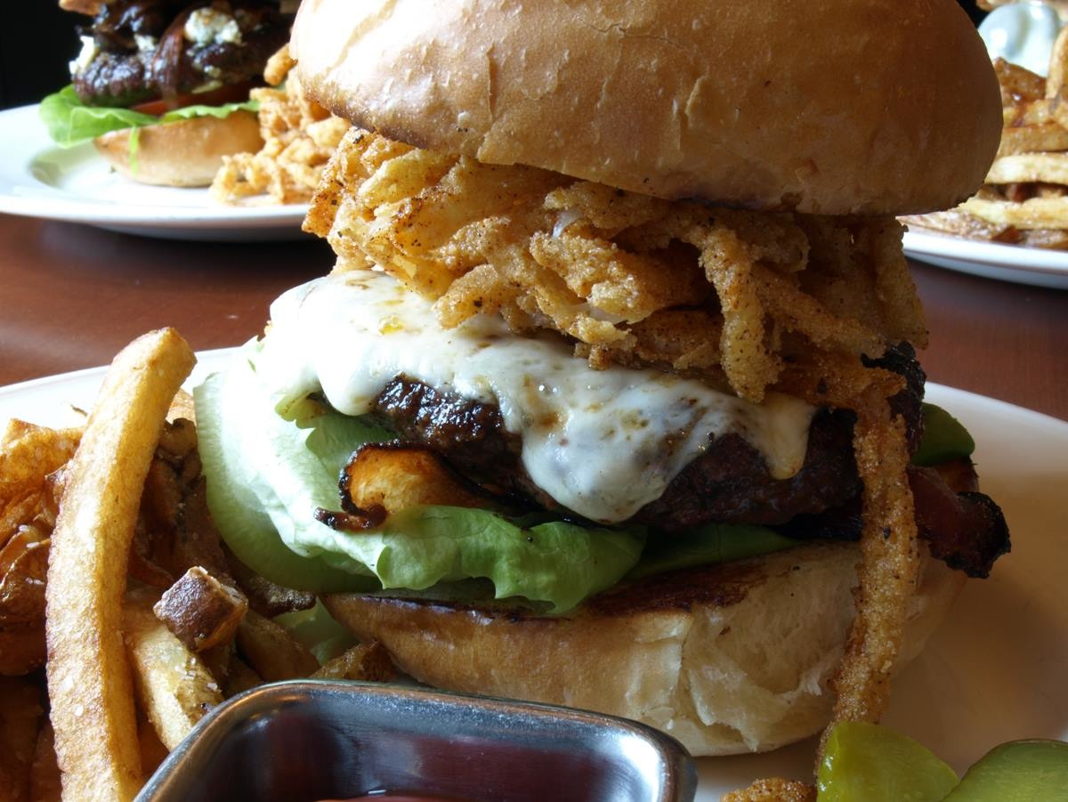 The Cowboy Burger from the Copper Door in Bedford and Salem, N.H., features brioche, bibb lettuce, tomato, bacon, chipotle, onion straws, pepper jack cheese and fries.
