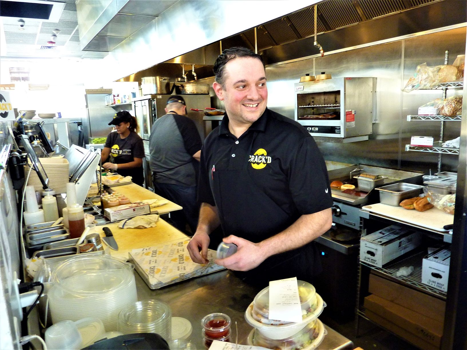 CRACK'D co-founder Danny Azzarello works the kitchen at his restaurant in Andover, Mass.