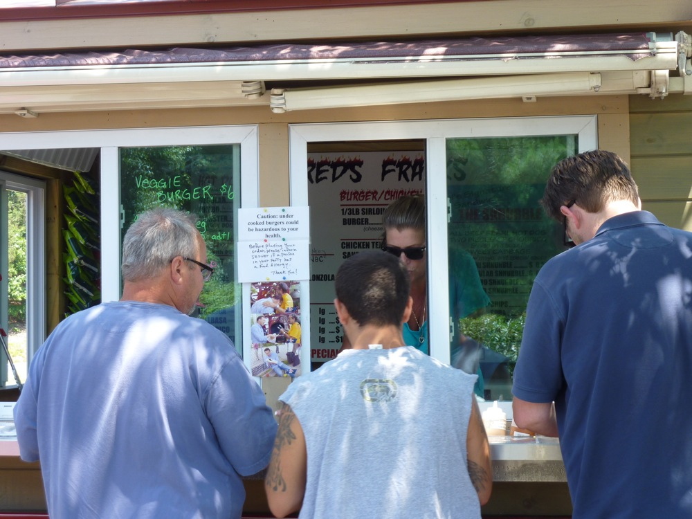 Synthia Ermao greets customers at the window at Fred's Franks in Wakefield, Mass.