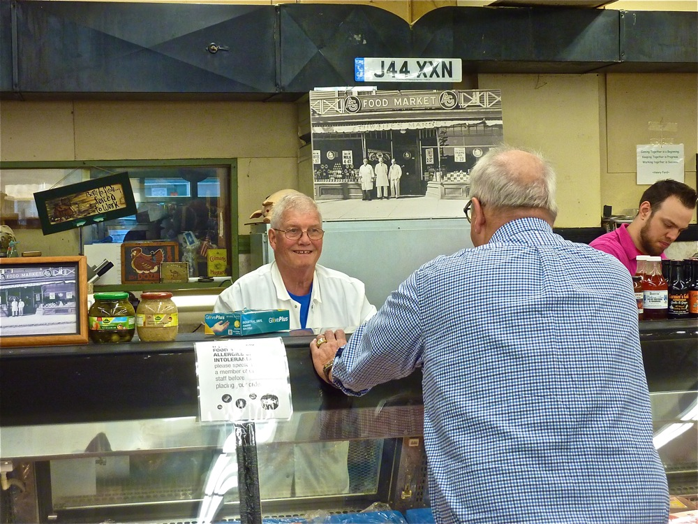 Ken Greenwood helps a customer at his store, Thwaites Market in Methuen, Mass.