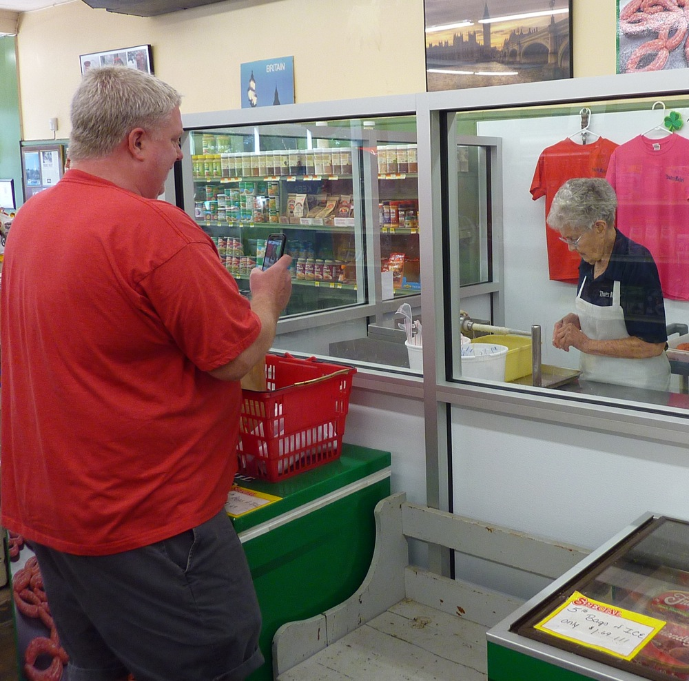 Impressed customer takes picture of Barbara Greenwood making sausages at Thwaites Market in Methuen, Mass.