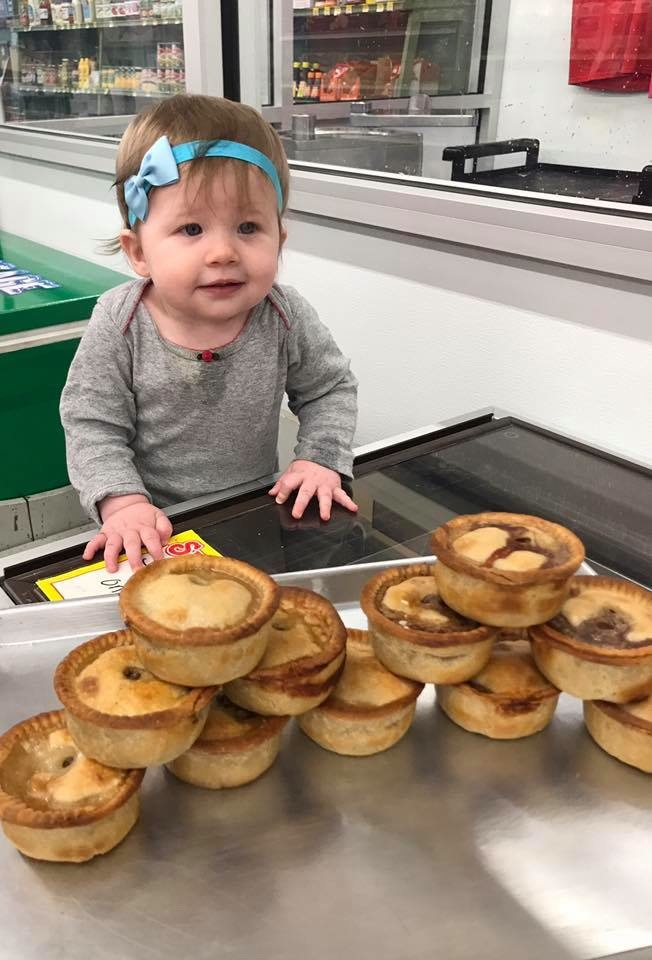 Abbey Hoffman's daughter, Pip, poses net to the English style pies at Thwaites Market in Methuen, Mass.